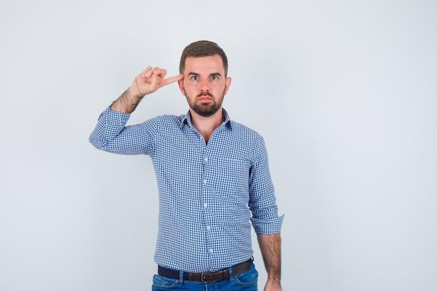 シャツ、ジーンズの寺院に人差し指を置き、真剣に見えるハンサムな男、正面図。
