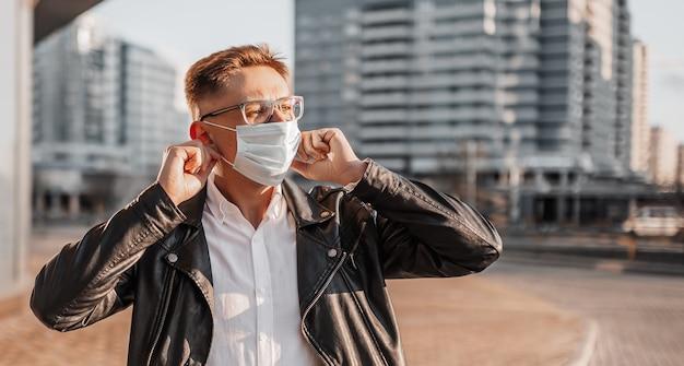도시 배경의 대도시 거리에서 안경을 쓰고 얼굴에 의료 보호 마스크를 쓰고 있는 잘생긴 남자