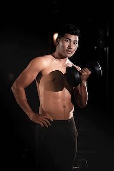 ハンサムな男がダンベルを上げる、筋肉の筋肉、フィット感としっかりした体、モデルのポーズのための運動を行う