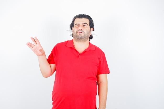 ハンサムな男が手を上げて、まばたきをし、赤いtシャツを着たナプキンを耳に当てて立っていて、優柔不断に見えます。正面図。