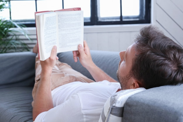 Handsome man reading a book in the sofa