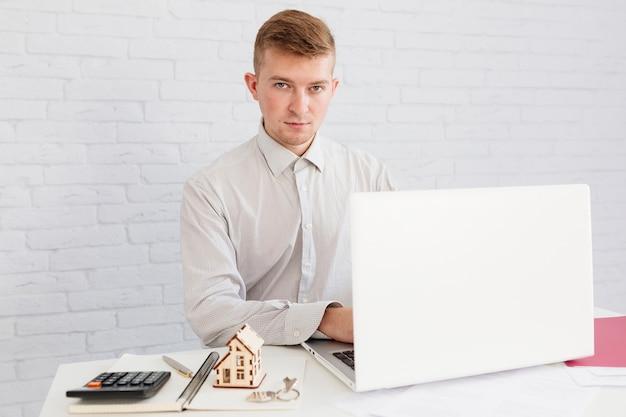Handsome man realtor at laptop