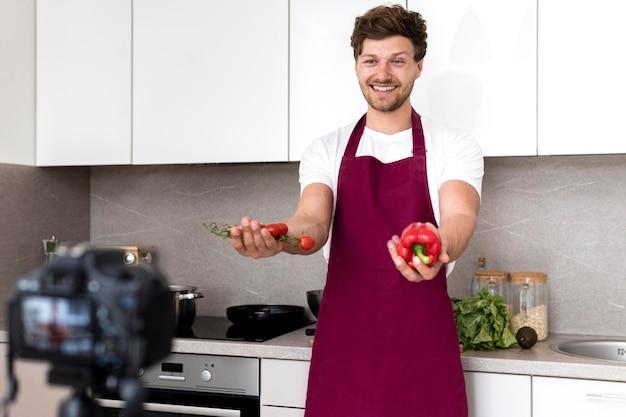 ハンサムな男が自宅で料理のビデオを記録