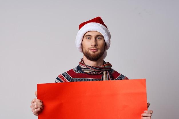 クリスマスライトの背景を宣伝するハンサムな男の赤い紙の看板