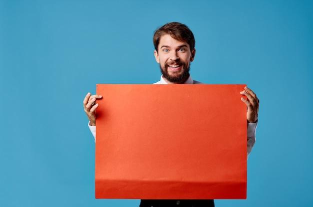 青い背景を宣伝するハンサムな男の赤いシートプレゼンテーション