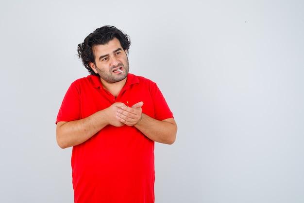 Uomo bello in maglietta rossa che tiene accendisigari nelle mani, in piedi con la sigaretta in bocca e guardando serio, vista frontale.