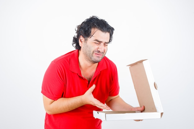 Handsome man in red t-shirt opening paper box, stretching hand toward it with disappointed manner and looking dismal , front view.