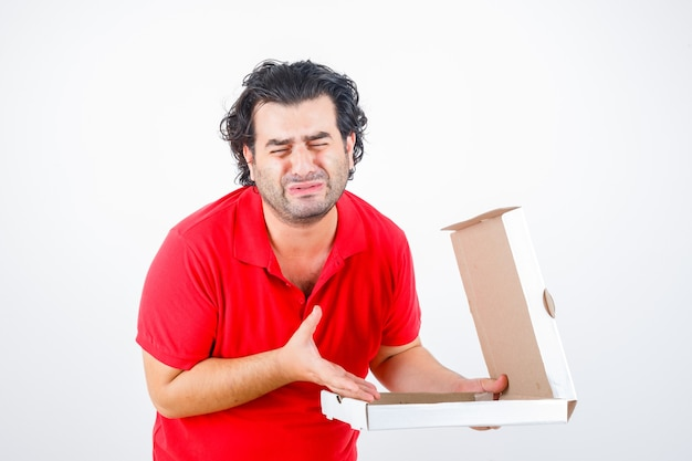 Handsome man in red t-shirt opening paper box, stretching hand toward it with disappointed manner and looking morose , front view.