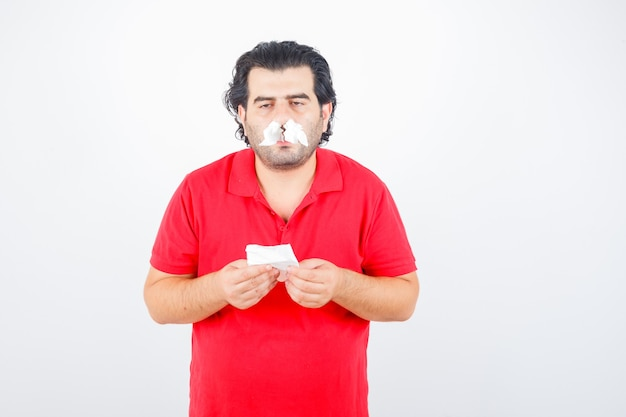 Uomo bello in maglietta rossa in piedi con tovaglioli nelle narici, tenendo il tovagliolo in mano e guardando serio, vista frontale