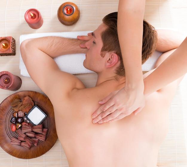 Красивый мужчина расслабился и наслаждается массажем спины глубоких тканей в спа-салоне.