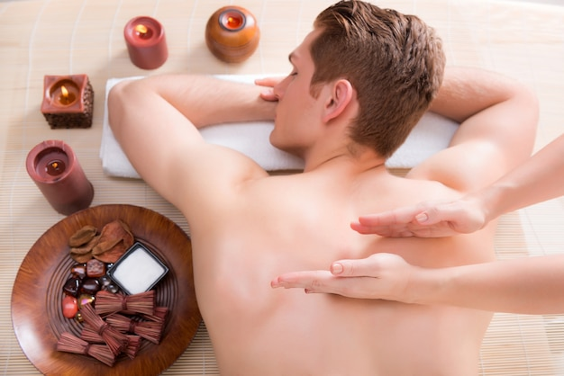 Handsome man relaxed and enjoying a deep tissue back massage at the spa salon.