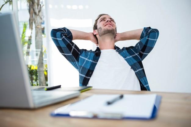 明るいオフィスで彼の机の椅子でリラックスしたハンサムな男