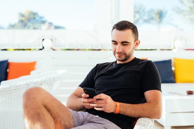 ビーチで電話でtupingをリラックスしてハンサムな男。
