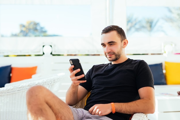 Handsome man relaxing tuping on phone on the beach.