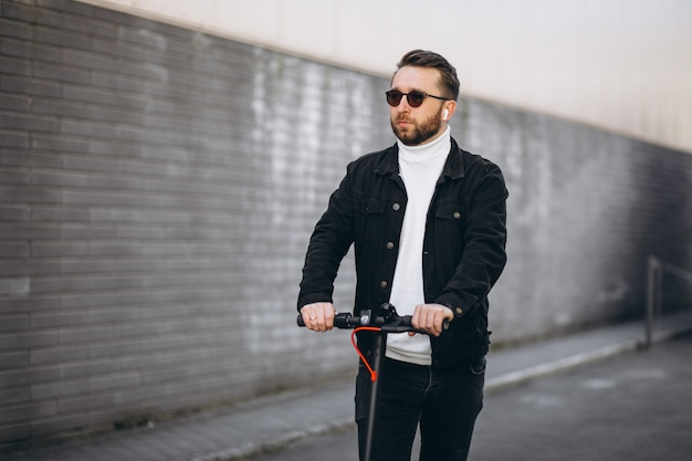Handsome man riding in town on scooter