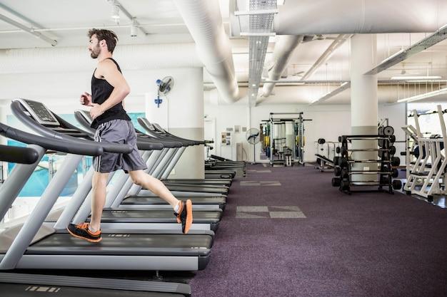 Handsome man running on treadmill