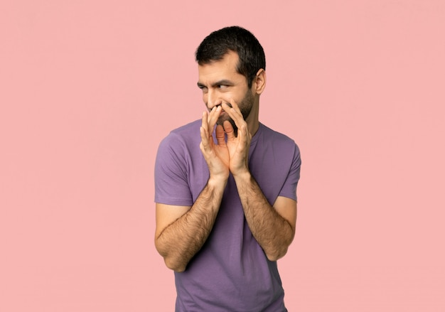 Handsome man scheming something on isolated pink background