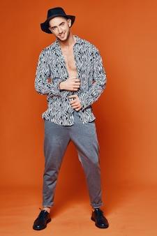 ハンサムな男の自信オレンジ背景スタジオモデル。高品質の写真