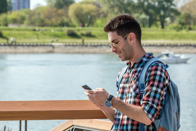 Handsome man sending text message.
