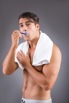 Handsome man shaving against dark background