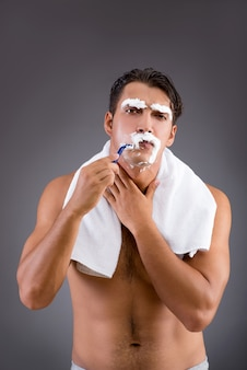Handsome man shaving against dark