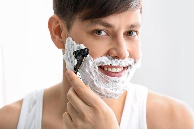 Красивый мужчина бреется на белой поверхности
