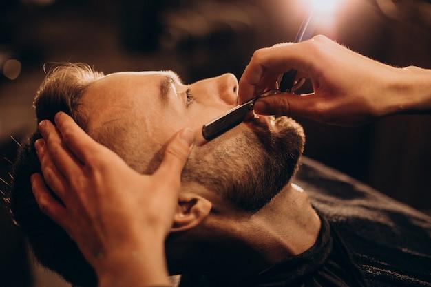 Красивый мужчина бреет бороду в парикмахерской