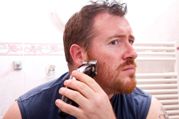 Handsome man shaving face with electric razor