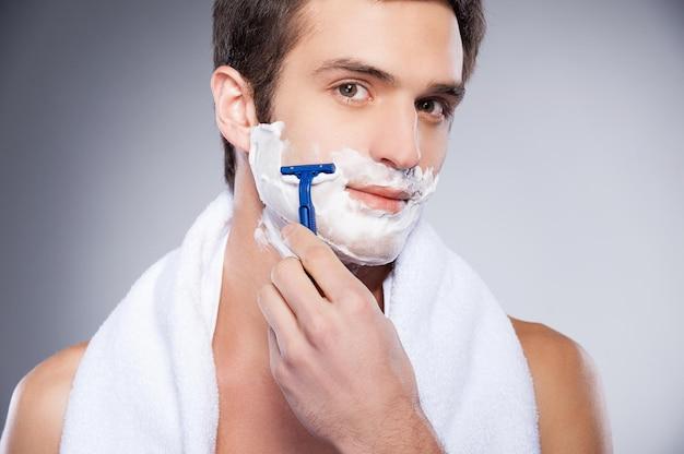 Красивый мужчина для бритья. красивый молодой человек без рубашки бреет лицо и смотрит в камеру, стоя изолированным на сером фоне