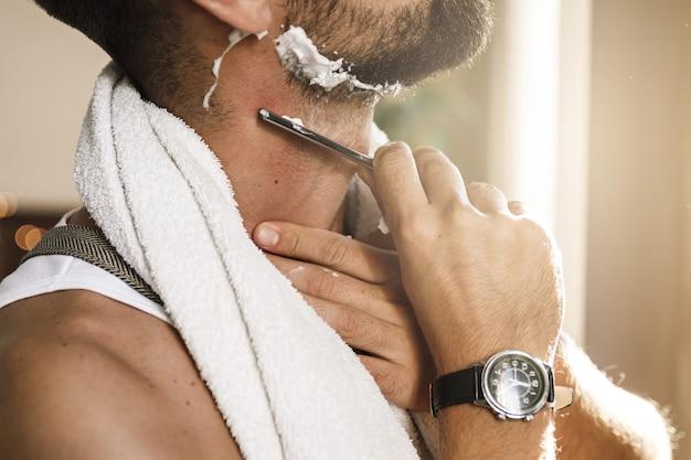 면도칼으로 그의 수염을 면도하는 잘 생긴 남자