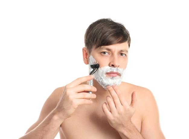 Красивый мужчина бреется на белом