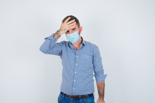 Handsome man in shirt, jeans, mask holding hand on head, having headache and looking exhausted , front view.