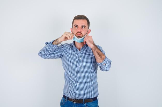 Uomo bello in camicia, jeans, maschera che tiene la maschera sotto il mento e che sembra serio, vista frontale.
