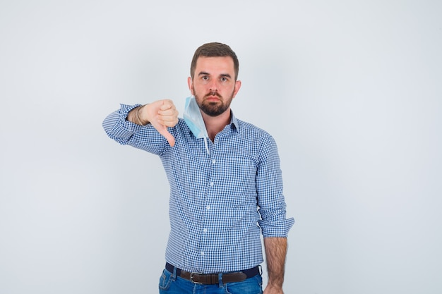 Handsome man in shirt, jeans, mask taking off mask, showing thumb down and looking displeased , front view.