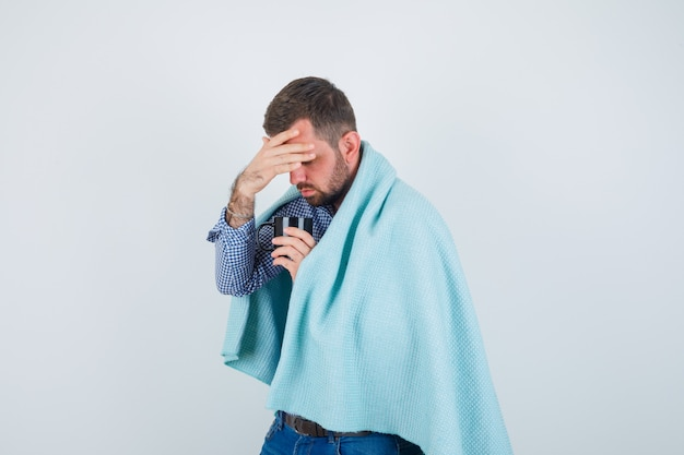 Handsome man in shirt, jeans, shawl holding cup of tea, having headache and looking exhausted , front view.