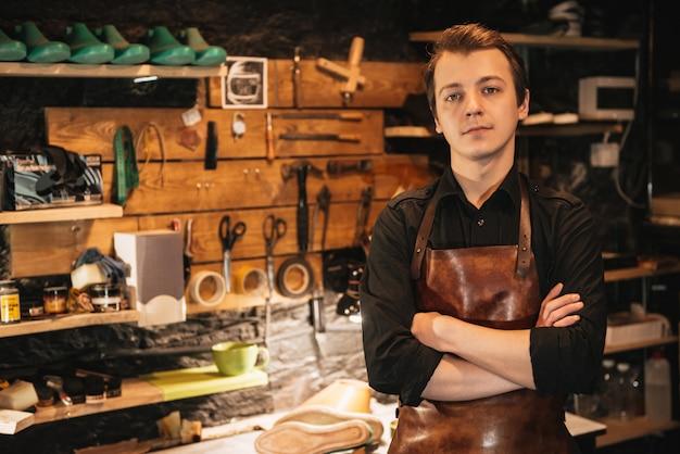 Handsome man shoemaker at footwear workshop