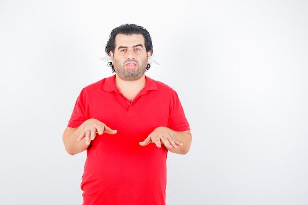 高さのジェスチャーを示し、赤いtシャツの耳にナプキンを持って立って、疲れているように見えるハンサムな男、正面図。