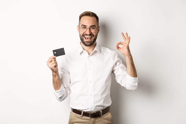 Uomo bello che mostra la sua carta di credito e segno giusto, raccomandando banca, in piedi copia spazio