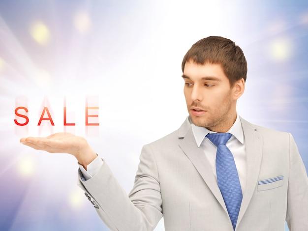 彼の手のひらの上で販売の言葉を示すハンサムな男