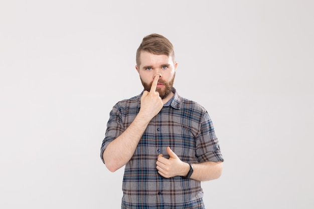 잘 생긴 남자는 미친 바보 같은 얼굴을 찡 그리기 또는 흰색 배경에 고립 된 표정을 보여줍니다. 얼굴에 재미있는 감정을 만들기.