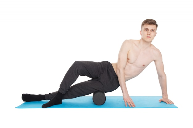 Handsome man shows exercises using a foam roller