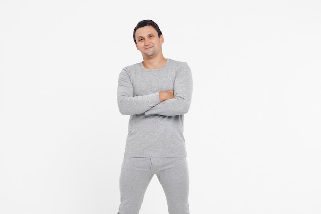Handsome man shows off gray clothes on white background