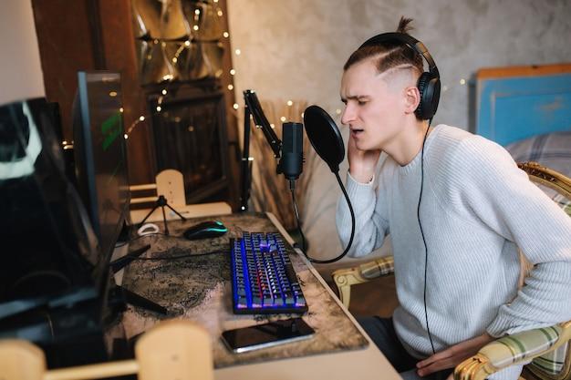마이크와 같은 전문적인 사운드 장비를 사용하는 컴퓨터 남자에 의해 집에서 잘 생긴 남자 노래