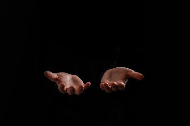 ハンサムな男は黒い背景に祈りを座っています。彼の手は神の祝福を祈っています。