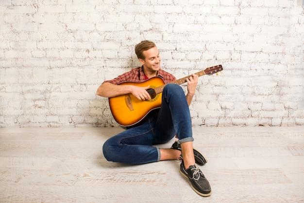 床に座ってギターを弾くハンサムな男