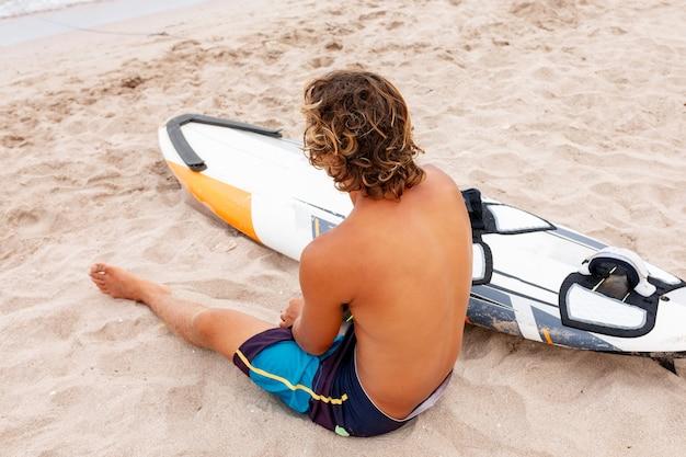 잘 생긴 남자는 흰색 빈 서핑 보드와 함께 해변에 앉아 바다 바다 해안에서 파도 서핑 자리를 기다립니다