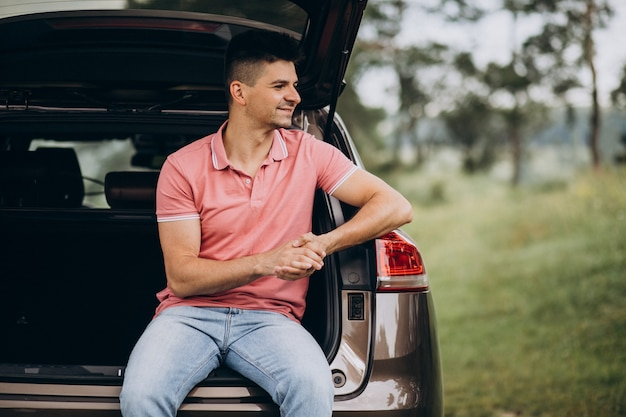 Uomo bello che si siede nella parte posteriore della macchina