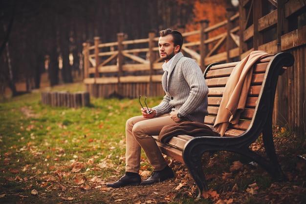 Handsome man sitting in bench