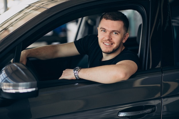 Handsome man sitting in car and testing it
