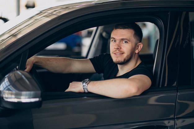 Uomo bello che si siede in automobile e che lo prova